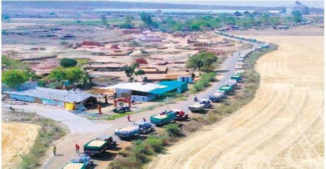 मध्य प्रदेश की विदिशा मंडी में गेहूं बेचने के लिए किसान अपनी बारी के इंतजार में, किसानों को कई-कई घंटों तक लाईन में लगे रहना पड़ता है