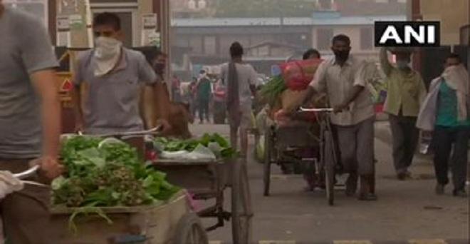 दिल्ली में कोरोना वायरस महामारी के बीच गाजीपूर फल और सब्जी मंडी से खरीदारी करने आए ग्राहक