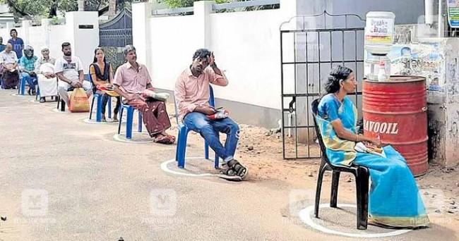केरल में एक राशन की दुकान के सामने सोशल डिस्टेंस का पालन करते लोग