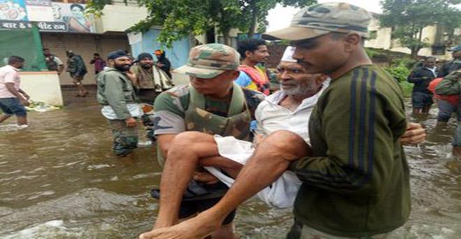 महाराष्ट्र के बाढ़ प्रभावित क्षेत्र में लोगों को सुरक्षित स्थान पर लेकर जाते हुए भारतीय सेेना के जवान