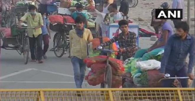 दिल्ली में कोरोना वायरस महामारी के बीच गाज़ीपुर फल और सब्जी मंडी से खरीदारी कर सामान लाते हुए ग्राहक