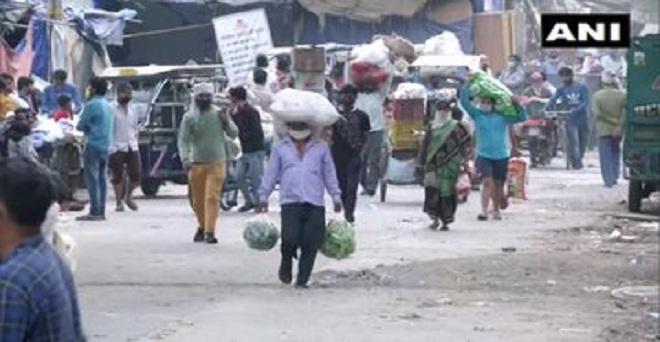 लॉकडाउन के बीच दिल्ली की ओखला फल और सब्जी मंडी से खरीददारी कर सामान ले जाते हुए दुकानदार