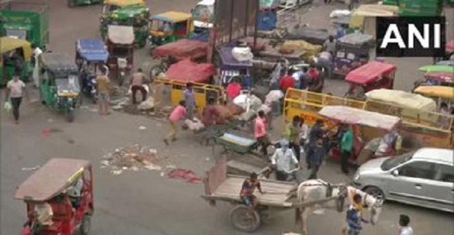 दिल्ली की आजादपुर फल और सब्जी मंडी के बाहर लोग खरीदारी कर सामान ले जाते हुए