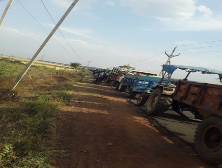 मध्य प्रदेश की विदिशा मंडी के बाहर गेहूं बेचने के लिए ट्रैक्टर ट्रॉलियों की लंबी कतार लगी है, यह हालत तो तब है जब किसान एसएमएस मिलने के बाद ही गेहूं बेचने पहुंच रहे हैं